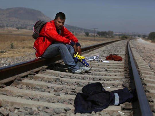 Mario Vazquez Santiago, a migrant from Guatemala, waits for a northbound train on the outskirts of Mexico City, Wednesday, Jan. 25, 2017. President Donald Trump signed two executive orders on Wednesday to jumpstart construction of a U.S.-Mexico border wall and strip funding for so-called sanctuary cities, which don't arrest or detain immigrants living in the U.S. illegally.