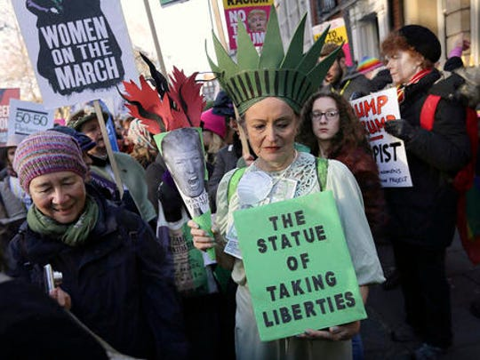 FILE- In this Jan. 21, 2017, file photo, demonstrators take part in the Women's March in London the day after the inauguration of U.S. President Donald Trump. Signs from the women's marches around the world are being saved as cultural treasures by museums, libraries and colleges.