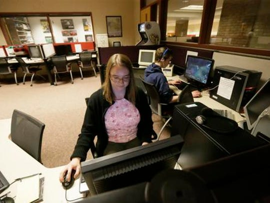 "In this May 20, 2016, Valerie Waldron, manager of the Computer and Video Game Archive, works on a terminal at the University of Michigan in Ann Arbor, Mich. The university's archive features over 7,000 titles - everything from time-honored favorites such as ""Pac-Man"" and ""Frogger"" to newer fare, including ""Call of Duty"" and ""Halo"" - on dozens of gaming systems. And unlike some other video game archives out there, students and members of the public alike are permitted to visit and play any game available, whether for research or just to relax."