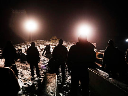 FILE- In this Dec. 1, 2016, file photo, military veterans walk onto a closed bridge to protest the Dakota Access oil pipeline across from police protecting the site in Cannon Ball, N.D. North Dakota Sen. John Hoeven said Tuesday, Jan. 31, 2017, that the Acting Secretary of the Army has directed the Army Corps of Engineers to proceed with an easement necessary to complete the Dakota Access pipeline.