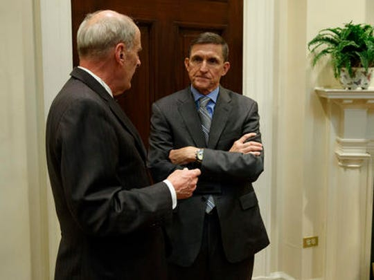 National Security Adviser Mike Flynn, right, talks with Ret. Gen. Keith Alexander before a meeting with President Donald Trump on cyber security in the Roosevelt Room of the White House in Washington, Tuesday, Jan. 31, 2017.