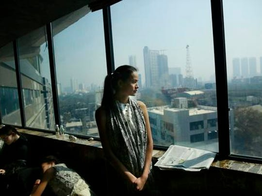 In this  Jan 30, 2017 photo, Anjali Lama, a transgender model from Nepal, looks out of a window of a hotel during a trial event for Lakme Fashion week in Mumbai, India. Growing up as the fifth son in a poor farming family in rural Nepal the dream to be a fashion model came late in life. First came a long, painful struggle to accept that he felt deeply female. It was a chance encounter with a group of transgender women that turned Lama's life around by putting her in touch with the Blue Diamond Society, an advocacy group for Nepal's LGBT community. In 2005 she came out to her friends and family as a transgender woman.