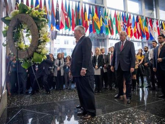 Secretary of State Rex Tillerson, center, accompanied by State Department Undersecretary for Political Affairs Tom Shannon, center right, stops a memorial wall plaques in the lobby of the State Department that honors employees who have given their lives in the line of duty, Thursday, Feb. 2, 2017, upon his arrival at the State Department in Washington.