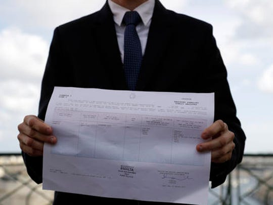 Politician Alex Mangion shows an official document where his chosen gender is registered, during an interview with the Associated Press, in Valletta, Wednesday, Feb. 1, 2017. Lithe and dapper in a navy-blue suit as he gazed at this capital city's storied Grand Harbor, Alex Mangion proudly described becoming Malta's first transgender politician, winning a local office on the conservative Nationalists' ticket in a country that until just a few years ago had been a last bastion in Western Europe of social norms largely dictated by the Catholic church.