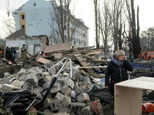 A woman speaks on her cell phone amonst the ruins of a building after shelling in Donetsk, eastern Ukraine, Friday, Feb. 3, 2017.  Heavy shelling hit both government- and rebel-controlled areas of eastern Ukraine as fighting continues Friday, and international monitors issued a sharp call for the sides to still their guns.