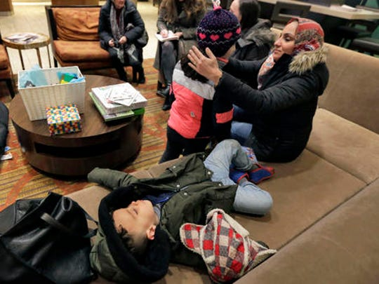 Hiba Alaskry, wife of Munther Alaskry, talks with their daughter Dima as their son Hassan naps on a couch in the lobby of their New York hotel, Friday, Feb. 3, 2017. Munther Alaskry and his family arrived at New York's Kennedy Airport after the Trump administration reversed course and said he and other interpreters who supported the U.S. military could come to America. They spent nearly a week in limbo in Baghdad, thinking their hopes of starting a new life free from death threats had been shattered.