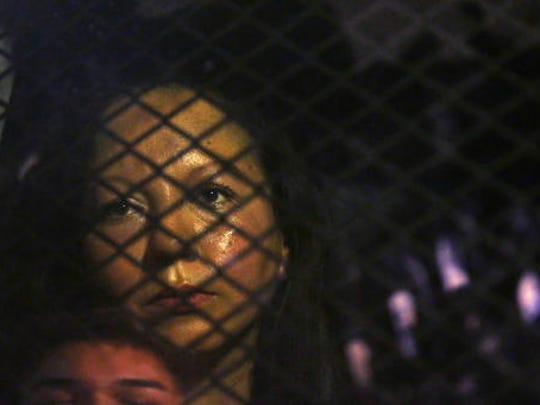 Guadalupe Garcia de Rayos is locked in a van that is stopped in the street by protesters outside the Immigration and Customs Enforcement facility Wednesday, Feb. 8, 2017, in Phoenix. Apparently fearing her deportation, activists blocked the gates surrounding the office near central Phoenix in what the Arizona Republic says was an effort to block several vans and a bus inside from leaving.