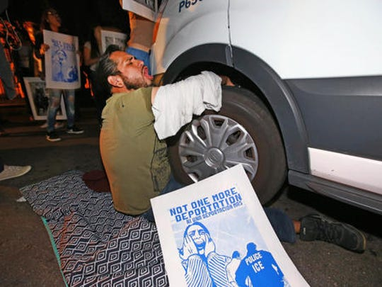 A protester locked himself to the van carrying Guadalupe Garcia de Rayos that is stopped by protesters outside the Immigration and Customs Enforcement facility, Wednesday, Feb. 8, 2017, in Phoenix. Apparently fearing her deportation, activists blocked the gates surrounding the office near central Phoenix in what the Arizona Republic says was an effort to block several vans and a bus inside from leaving. Police arrested several protesters Wednesday night after they blocked enforcement vans.