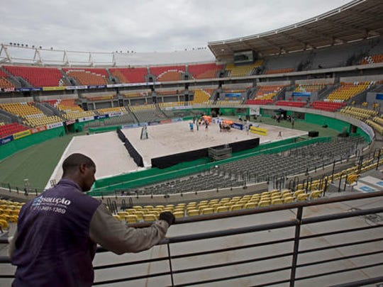 In this Feb. 4, 2017 photo, a worker paints a fence at the Olympic Tennis Center inside Olympic Park in Rio de Janeiro, Brazil. This venue is one of four permanent arenas being run by the federal government, and was used for a one-day beach volleyball tournament, in a city with endless sand and beaches.