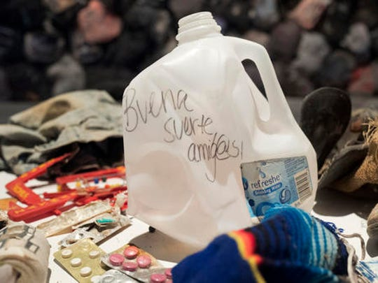 "An empty water jug is one of hundreds of items left behind by migrants illegally crossing the border into the Sonoran Desert of southern Arizona on display in the ""State of Exception"" exhibit, Friday, Feb. 10, 2017 in New York. The exhibit at the Sheila C. Johnson Design Center at the Parsons School of Design continues through April 17. Writing on the jug reads in Spanish, ""buena suerte amigas"" or, ""good luck friends."""