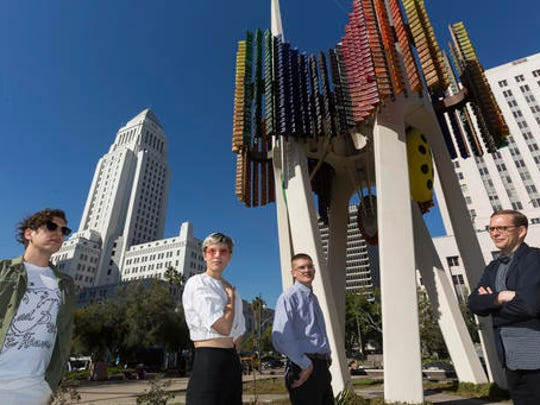 "In this Wednesday, Feb. 1, 2017, photo members of the Triforium project, from left, Jona Bechtolt, Claire Evans, Tom Carroll, and Tanner Blackman,  pose for a photo with Joseph L. Young's Triforium a ""polyphonoptic"" public sculpture at the Fletcher Bowron Square downtown Los Angeles.  For 40 years Joseph Young festooned public buildings, open spaces and private places across his adopted city of Los Angeles with dozens of brilliant, larger-than-life artworks.  Mocked for 42 years as pointless and silly looking, the six-story, space-age-like structure may finally get a second chance, thanks to a $100,000 innovation grant."
