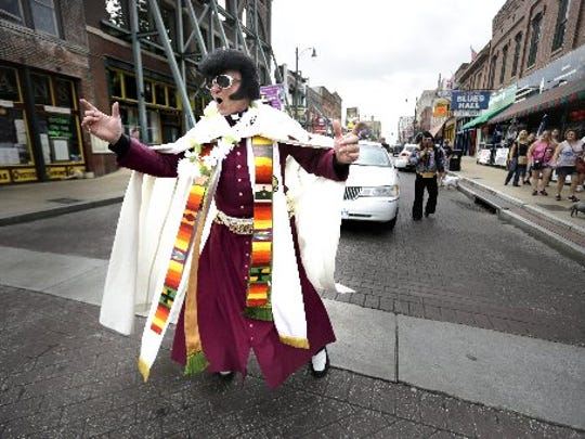 "Dorian Baxter, who is also known as ""The Reverend Elvis Priestly"", leads a parade down Beale Street in August 2016  to honor the late King of Rock and Roll, Elvis Presley. Baxter was ordained an Anglican Priest in 1983 and uses the music of Elvis Presley at his services at Christ the King Graceland Church in Newmarket, Ontario."