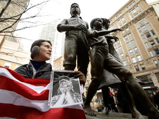 """Molly Hitt, of Boston, displays an American flag while standing in front of a memorial to the Irish potato famine, right, during a rally called """"We Will Persist,"""" Tuesday, Feb. 21, 2017, in Boston. According to organizers the rally was held to send a message to Republicans in Congress and the administration of President Donald Trump that they will continue to press for immigration rights and continued affordable healthcare coverage."""