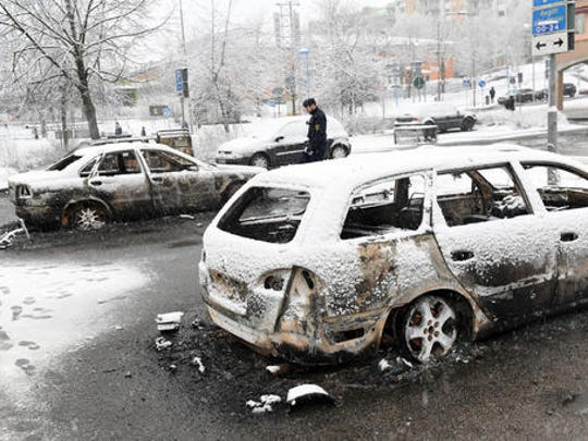 In this picture taken on Monday, Feb. 20, 2017,a policeman investigates a burned out car in the suburb of Rinkeby outside Stockholm. Police in Sweden said Tuesday they were investigating riots that broke out overnight in a predominantly immigrant Stockholm suburb after officers arrested a suspect on drug charges. Spokesman Lars Bystrom said unidentified people, including some wearing masks, threw rocks at police, set cars on fire and looted shops in Rinkeby, north of Stockholm.