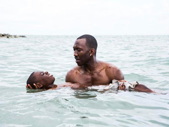 """This image released by A24 shows Alex Hibbert, foreground, and Mahershala Ali in a scene from the film, """"Moonlight."""""""