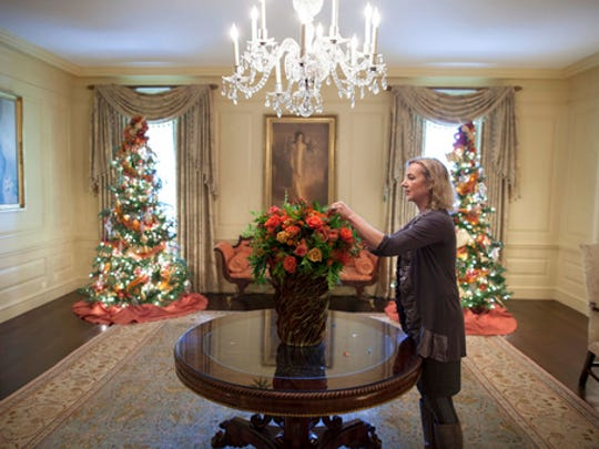 "In this Dec. 1, 2010 photo provided by Stichting Kunstboek, Laura Dowling completes a holiday arrangement of peach and coral roses in a magnolia leaf vase in the Vermeil Room, before the launch of the White House Christmas season, with the Aaron Shikler portrait of First Lady Jacqueline Kennedy in the background at the White House in Washington. The photograph is featured in the book ""Floral Diplomacy: At the White House,"" by Laura Dowling."