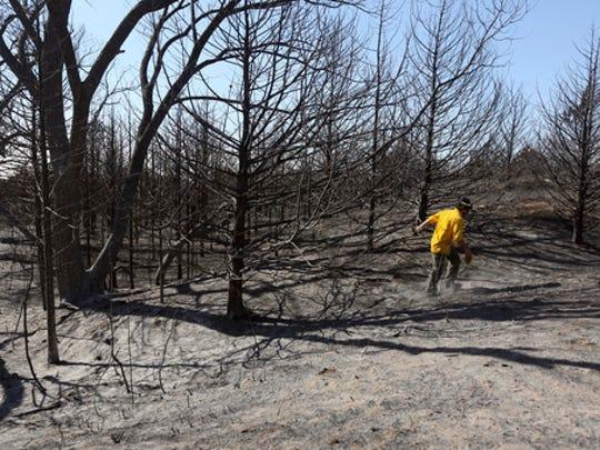 Firefighter Travis Pohlman checks for hot spots in