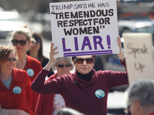 Judy Miller of Evergreen, Colo., holds up a placard during a march around the State Capitol to mark International Women's Day on Wednesday, March 8, 2017, in Denver. More than 1,000 women--and men--took part in the Denver march, one of many staged across the country by organizers of January's Women's March. The action called on women to stay home from work and not spend money in stories or online to show their economic clout on America's fabric.