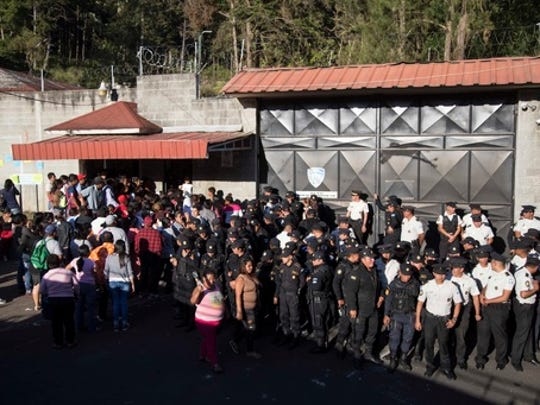 National Police guard the entrance to the children's shelter Virgin of the Assumption Safe Home where people gather in San Jose Pinula, Guatemala, Wednesday, March 8, 2017. At least 19 people have died after a fire at the shelter, which was created to house children who were victims of abuse, homelessness or who had completed sentences at youth detention centers and had nowhere else to go, the spokesman for Guatemala's volunteer fire departments said.
