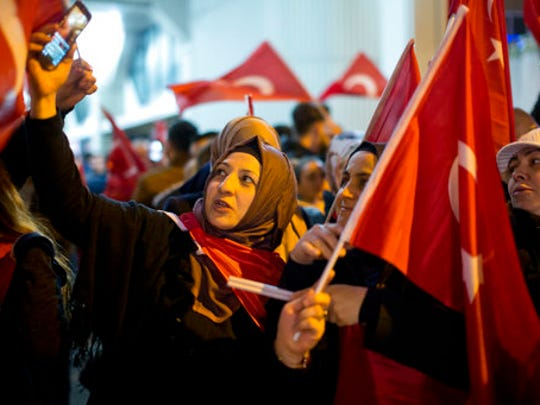 """Demonstrators wave turkish flags outside the Turkish consulate in Rotterdam, Netherlands, Saturday, March 11, 2017. Turkish Foreign Minister Mevlut Cavusoglu was due to visit Rotterdam on Saturday to campaign for a referendum next month on constitutional reforms in Turkey. The Dutch government says that it withdrew the permission for Cavusoglu's plane to land because of """"risks to public order and security."""""""