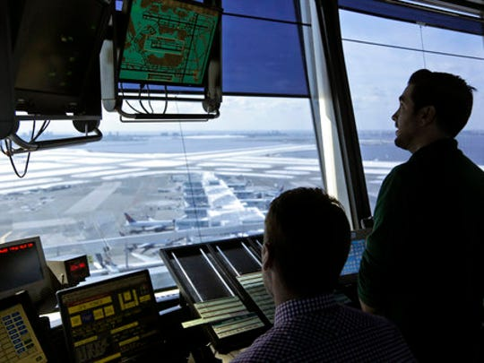 Air traffic controllers work in the tower at John F.