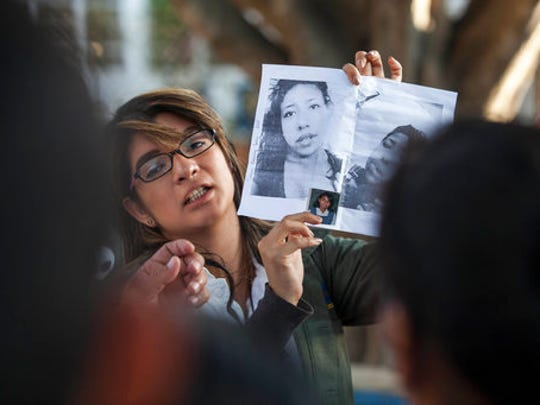 In this March 8, 2017 photo, a doctor shows photos of the victims in an attempt to identify them after a fire at the Virgen de la Asuncion Safe Home, outside the Roosevelt Hospital in Guatemala City. When firefighters entered the home for troubled youths, they discovered more than two dozen girls on the floor of a locked room, most of them dead.