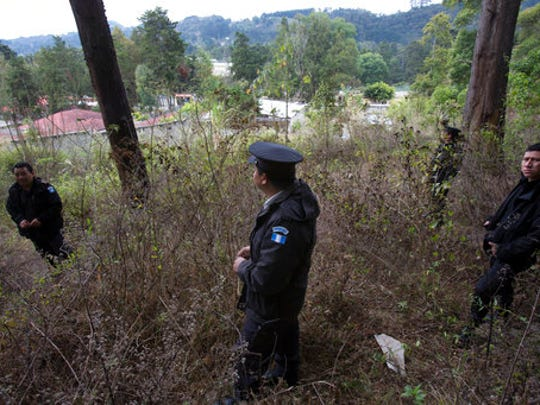In this March 15, 2017 photo, police stand guard in the woods near the Virgen de la Asuncion Safe Home, in San Jose Pinula, Guatemala. The children's shelter, located on a hill 14 miles southeast of Guatemala City, protected by high walls and barbed wire, is surrounded by an idyllic pine forest covered with mist every morning. The forest and ravines have offered hiding places for more than 100 children who have escaped what they consider a jail.
