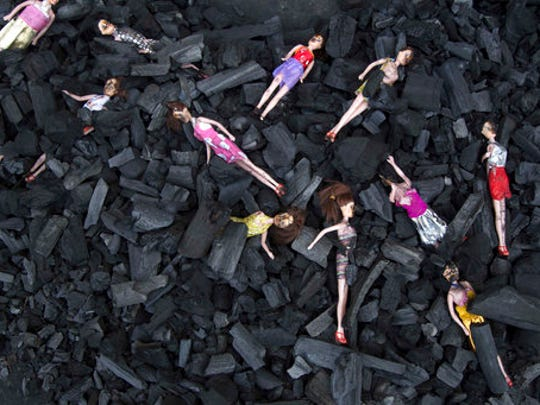 FILE - In this March 9, 2017 file photo, charred-stained dolls placed on a bed of charcoal are part of an artists' installation placed at the front gate of the presidential house in remembrance of the victims of a fire at the Virgen de la Asunción Safe Home, in Guatemala City. The girls' hell at the government-run home began long before the deadly fire, as documented in several warnings from four different agencies. At least two orders for closure were ignored.