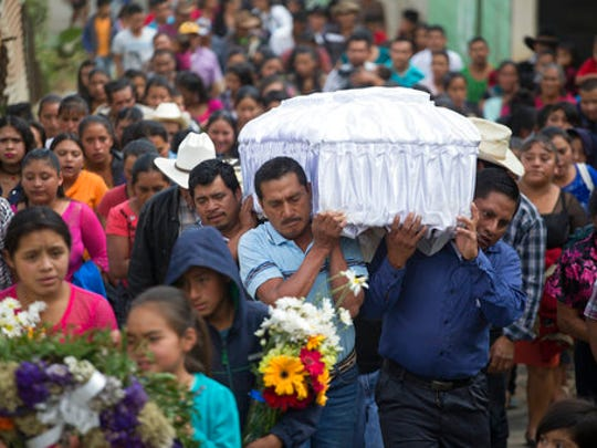 FILE - In this March 12, 2017 file photo, people carry the coffin of 14-year-old Ana Roselia Perez Junay, who died in the fire at Virgen de la Asunción Safe Home, to the cemetery in Zaragoza, Guatemala. The majority of the children at the shelter had committed no crime, but were youths sent there by the courts for various reasons. Most came from families so poor they could not afford the $50 lawyers' fees to get their children out.