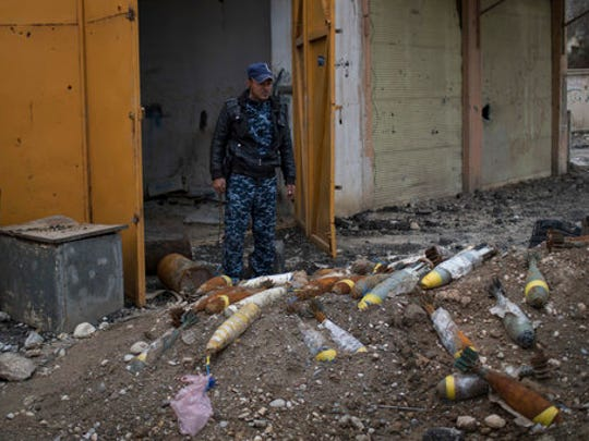 A Federal Police stands next to unexploded bombs left by Islamic State militants on the western side of Mosul, Iraq, Wednesday, March 22, 2017.