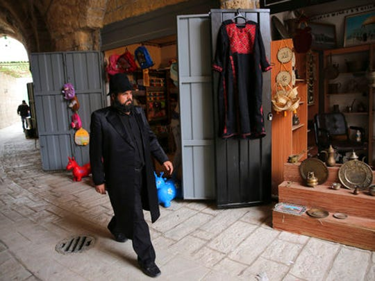 """In this Wednesday, March 22, 2017 photo, a Palestinian actor dressed as ultra Orthodox Jew walks during a shoot of the """"Heaven's Gate"""" movie in a recreated alleyway of Jerusalem's Old City in Khan Younis, Gaza Strip. Surrounded by militant training sites on uprooted Jewish settlement lands, the first movie set in the Gaza Strip is growing, depicting the history-rich, volatile alleyways of Jerusalem's Old City."""