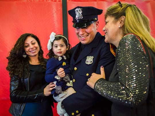 Matias Ferreira, center, celebrates with his 2-year-old daughter, his wife, left, and his mother during his graduation from the Suffolk County Police Department Academy at the Health, Sports and Education Center in Suffolk, Long Island, New York, Friday, March 24, 2017. Matias Ferreira, a former U.S. Marine Corps lance corporal who lost his legs below the knee when he stepped on a hidden explosive in Afghanistan in 2011, is joining a suburban New York police department. The 28-year-old graduated Friday from the Suffolk County Police Academy on Long Island following 29 weeks of training.