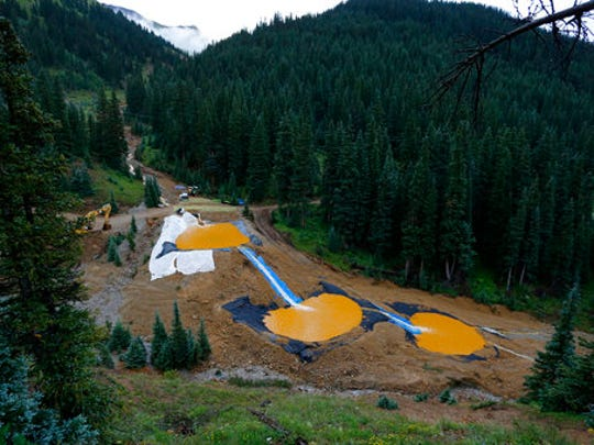 In this Aug. 12, 2015 photo, mine wastewater flows through a series of retention ponds built to contain and filter out heavy metals and chemicals from the Gold King Mine chemical accident in the spillway about 1/4 mile downstream from the mine, outside Silverton, Colo. Farmers, business owners and residents initially said they suffered $1.2 billion in lost income, property damage and personal injuries from the 2015 spill at the Gold King Mine. The total now appears to be about $420 million after attorneys for a handful of New Mexico property owners slashed their claims by $780 million.