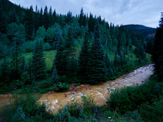 In this Aug. 12, 2015, photo, the water of the Cement Creek is yellow-tinged as it flows down a valley just downstream from the Gold King Mine, where a wastewater accident several days earlier had occurred, outside Silverton, Colo. Farmers, business owners and residents initially said they suffered $1.2 billion in lost income, property damage and personal injuries from the 2015 spill at the Gold King Mine. The total now appears to be about $420 million after attorneys for a handful of New Mexico property owners slashed their claims by $780 million.