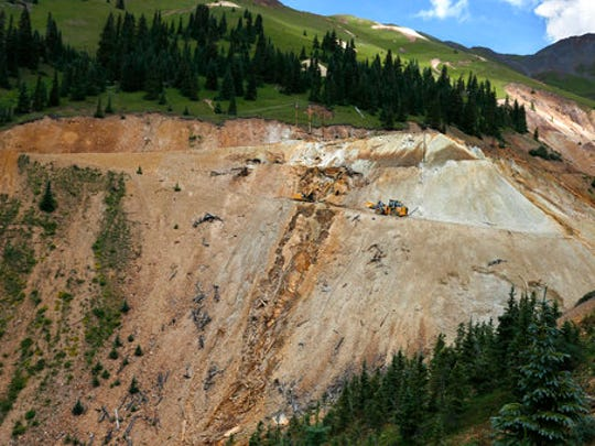 In this Aug. 12, 2015 photo, Environmental Protection Agency contractors use heavy machinery to repair damage at the site of the blowout at the Gold King Mine, which triggered a spill of toxic wastewater, outside Silverton, Colo. Farmers, business owners and residents initially said they suffered $1.2 billion in lost income, property damage and personal injuries from the 2015 spill at the Gold King Mine. The total now appears to be about $420 million after attorneys for a handful of New Mexico property owners slashed their claims by $780 million.