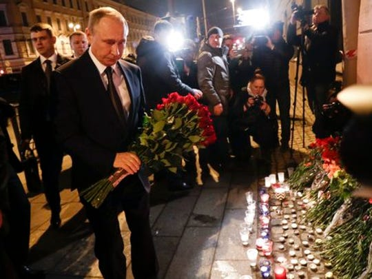 Russian President Vladimir Putin, left, lays flowers at a place near the Tekhnologichesky Institut subway station in St.Petersburg, Russia, Monday, April 3, 2017. A bomb blast tore through a subway train deep under Russia's second-largest city Monday, killing several people and wounding many more in a chaotic scene that left victims sprawled on a smoky platform.