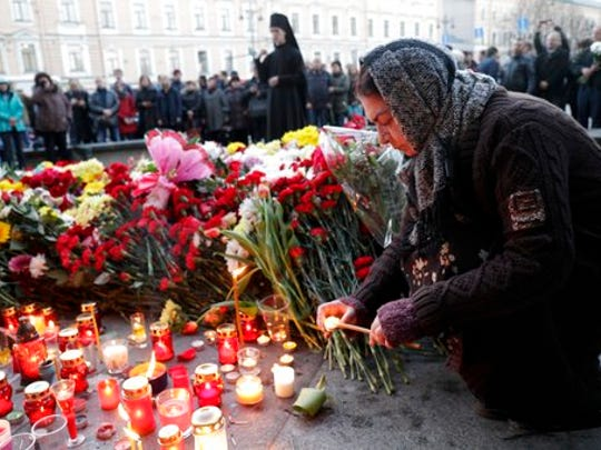 A woman lights a candle at a symbolic memorial outside Technologicheskiy Institute subway station in St. Petersburg, Russia, Tuesday, April 4, 2017.  A bomb blast tore through a subway train deep under Russia's second-largest city St. Petersburg Monday, killing several people and wounding many more in a chaotic scene that left victims sprawled on a smokey platform.