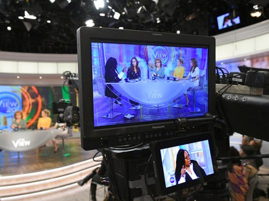 "In this March 21, 2017 photo released by ABC, co-hosts, from left, Whoopi Goldberg, Sunny Hostin, Joy Behar, Sara Haines and Jedediah Bila appear on a monitor during a broadcast of ""The View,"" in New York. The unquenchable thirst for chatter about President Donald Trump has changed the dynamics of a fierce daytime television competition much as it has in late-night TV. ""The View"" has spent more time talking politics with the arrival of a new administration, stopping the momentum of its rival ""The Talk,"" which sticks to pop culture."