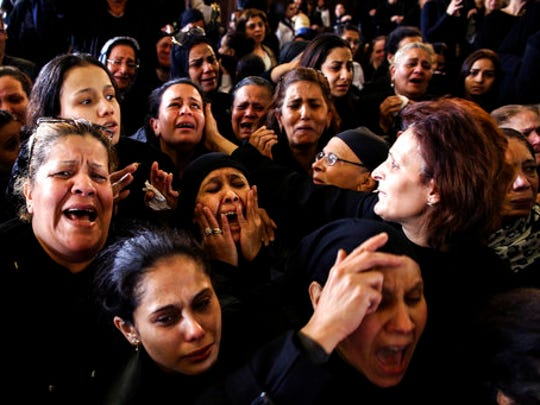 Women cry during the funeral for those killed in a