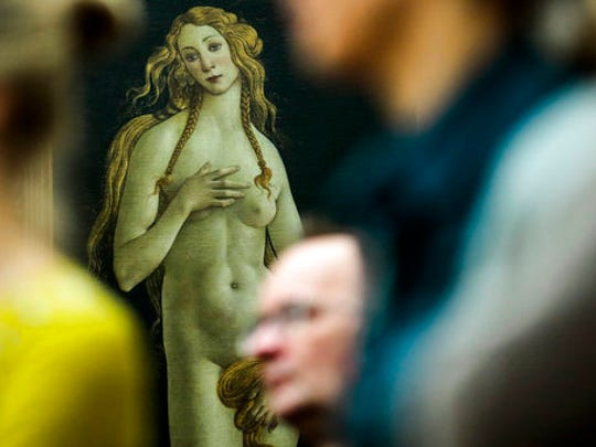 """In this Thursday, Jan. 15, 2015 file photo people stand in front of the 'Venus' by Italian painter Sandro Botticelli during a news conference about the planned exhibition 'The Botticelli Renaissance' in Berlin. A new exhibition of Italian Renaissance master Sandro Botticelli's paintings opens this weekend in Boston, """"Botticelli and the Search for the Divine"""" at Boston's Museum of Fine Arts."""