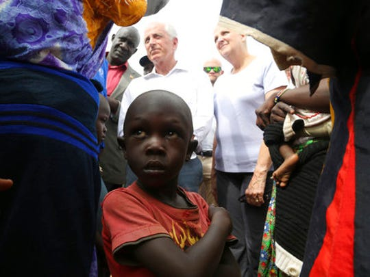 A child looks up while Senator Bob Corker, center left, speaks to recent refugees from South Sudan at a registration center in Bidi Bidi, Uganda, Friday, April 14, 2017. Sen. Bob Corker of Tennessee, the Republican chairman of the Foreign Relations Committee, strongly defended U.S. foreign assistance on Friday while visiting the world's fastest growing refugee crisis in northern Uganda, just across the border from war-torn South Sudan.