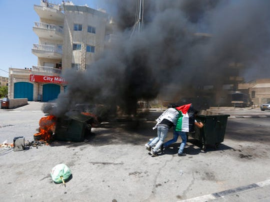 Palestinians push a container during clashes with Israeli forces following a rally in support of Palestinian prisoners in the West bank City of Bethlehem, Monday, April 17, 2017. An activist said more than 1,500 Palestinian prisoners have launched an open-ended hunger strike to demand better conditions in Israeli prisons, including more contact with relatives, and an end to Israel's practice of detentions without trial.