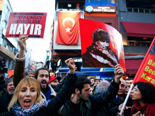 Supporters of the 'no' vote, (Hayir in Turkish) one holding a banner of modern Turkey's founder Mustafa Kemal Ataturk, chant slogans during a protest against the referendum outcome, in Istanbul, Tuesday, April 18, 2017. Hundreds of people are queuing in front of Turkey's election board in capital Ankara to submit petitions requesting that the electoral authority reverse a controversial decision during Sunday's referendum to accept ballots without official stamps, as required by Turkish law.