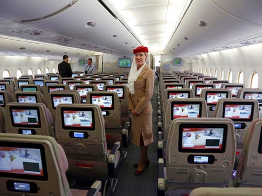 FILE- In this Wednesday, March 12, 2014 file photo, a stewardess stands inside an Emirates A380 aircraft, the world's largest passenger airline, during the fourth Indian Aviation show at Begumpet airport in Hyderabad, India. The Middle East's biggest airline says it is reducing flights to the United States because of a drop in demand caused by tougher U.S. security measures and attempts by the Trump administration to ban travelers from a number of Muslim-majority nations.