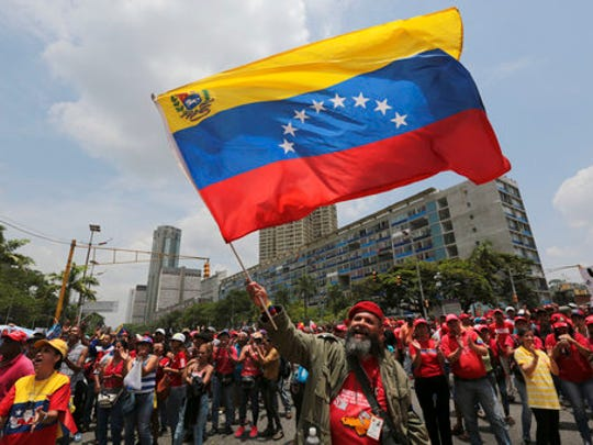 """A government supporter waves a national flag during a march in Caracas, Venezuela, Wednesday, April 19, 2017. Opponents of President Nicolas Maduro called on Venezuelans to take to the streets on Wednesday for what they dubbed the """"mother of all marches"""" against the embattled socialist leader. Government supporters are holding their own counter demonstration."""