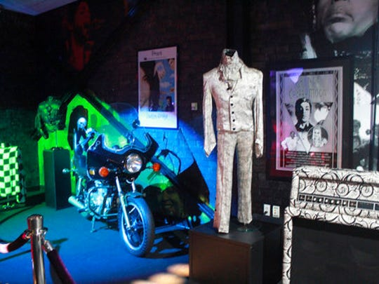 "FILE - In this Nov. 2, 2016 file photo, a Prince costume and motorcycle are on display at Prince's Paisley Park in Chanhassen, Minn. Paisley Park, home and studio of the late musician Prince, is open for public tours. At his home and recording studio-turned-museum, a full four days of events are on tap for the one-year anniversary of his death on April 21, 2016, ranging from concert performances by the great one's former band mates to panel discussions on his legacy. Fans who can't afford those high-dollar tickets can head to a street party outside the club he made famous in ""Purple Rain."""