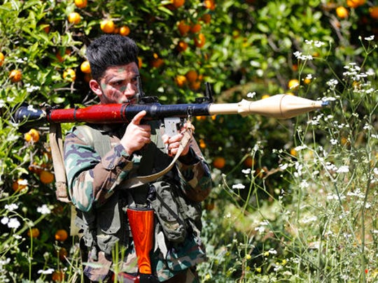 A Hezbollah fighter holds an RPG as he takes his position between orange trees, at the coastal border town of Naqoura, south Lebanon, Thursday, April 20, 2017. Hezbollah organized a media tour along the border with Israel meant to provide an insight into defensive measures established by the Israeli forces along the southern frontier in the past year in preparation for any future conflict.