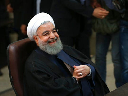 FILE- In this Friday, April 14, 2017 file photo, Iranian President Hassan Rouhani smiles as he attends at the Interior Ministry to register his candidacy for the May 19 presidential elections, in Tehran, Iran. Iranian state TV said Thursday, April 20, that the body charged with vetting candidates has disqualified former hard-line President Mahmoud Ahmadinejad from running in next month's presidential election. It carried an Interior Ministry statement saying that Rouhani has been approved to run for re-election.