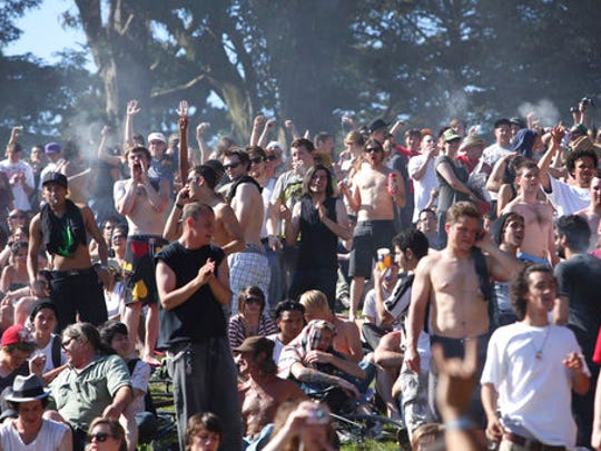 FILE - In this April 20, 2009, file photo, a large crowd cheers as the time reaches 4:20 p.m. on Hippie Hill in Golden Gate Park in San Francisco. Thursday, April 20, 2017, marks marijuana culture's high holiday, 4/20, when college students gather - at 4:20 p.m. - in clouds of smoke on campus quads and pot shops in legal weed states thank their customers with discounts.
