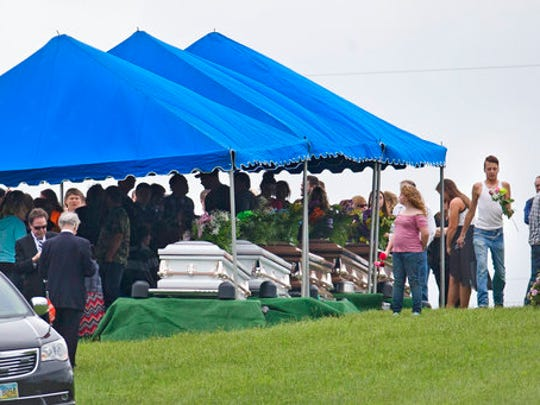 FILE – In this May 3, 2016, file photo, mourners gather around caskets for six of the eight members of the Rhoden family found shot April 22, 2016, at four properties near Piketon, Ohio, during funeral services at Scioto Burial Park in McDermott, Ohio. Ohio State Attorney General Mike DeWine and Pike County Sheriff Charles Reader planned a news conference Thursday, April 13, 2017, about the unsolved killings, as the anniversary of the massacre approaches.